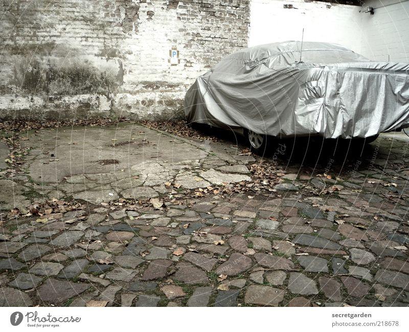 [HH10.1] ganzautokondom. weiß Wand grau Mauer Gebäude PKW frei stehen Sicherheit trist Schutz Kopfsteinpflaster Fahrzeug Parkplatz Herbstlaub Schutzschild