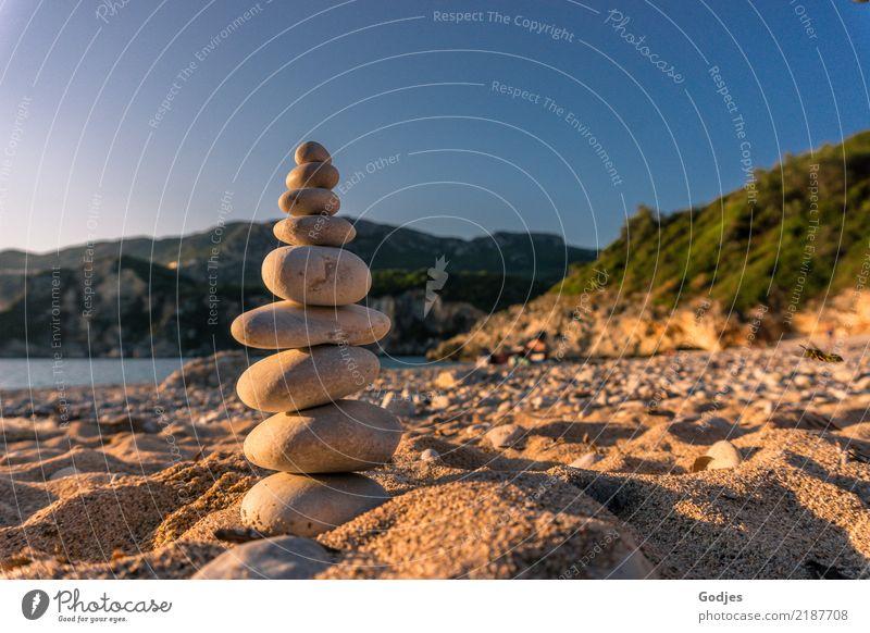 Steinpyramide auf einem Sandstrand mit Bergen und Wasser im Hintergrund Landschaft Wolkenloser Himmel Sommer Schönes Wetter Baum Sträucher Strand Bucht stehen