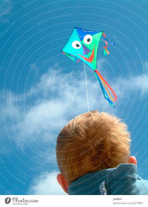 Kind lässt Drachen steigen Farbfoto Außenaufnahme Nahaufnahme Textfreiraum links Textfreiraum oben Tag Rückansicht Blick nach vorn Sonne Himmel Wolken Wind