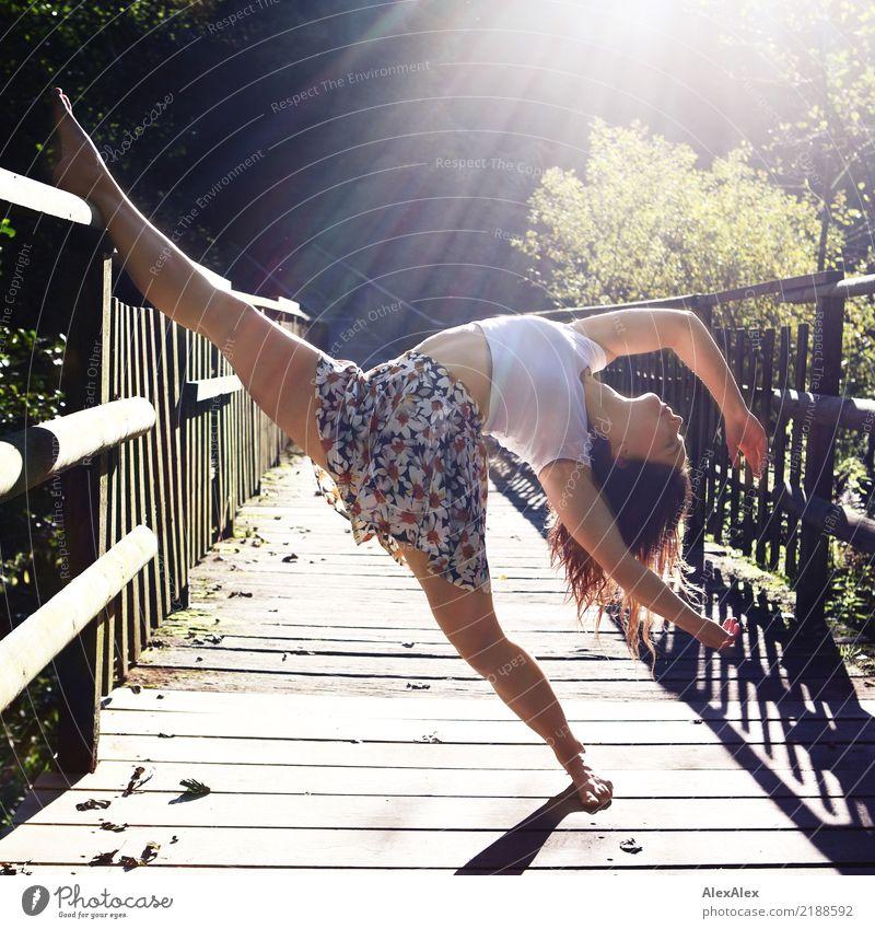 Junge, sehr sportliche Frau steht barfuß auf einer Holzbrück im Gegenlicht im Wald und lehnt ein Bein auf das Geländer bei der Tanzpose, die sie macht. Sie hat ein bauchfreies Top an und ist barfuß.