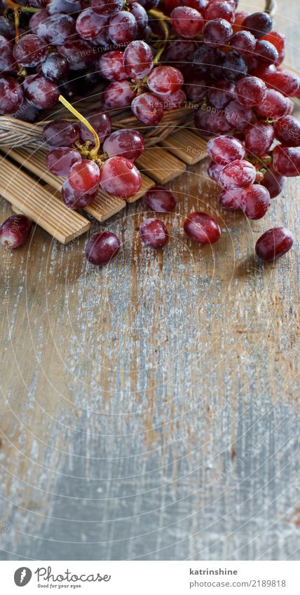 Rote Trauben auf einem alten Holztischabschluß oben Frucht Ernährung Tisch Herbst dunkel frisch retro rot Ackerbau Beeren Lebensmittel Weintrauben Weinrebe