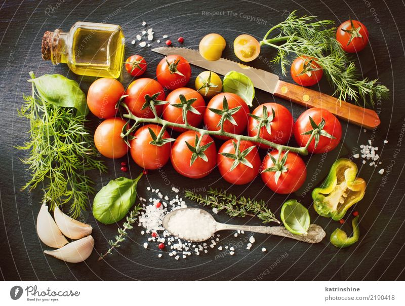 Kirschtomaten, Kräuter und Olivenöl auf einem dunklen Brett Gemüse Vegetarische Ernährung Diät Flasche Löffel Tisch Blatt dunkel frisch hell natürlich grün rot
