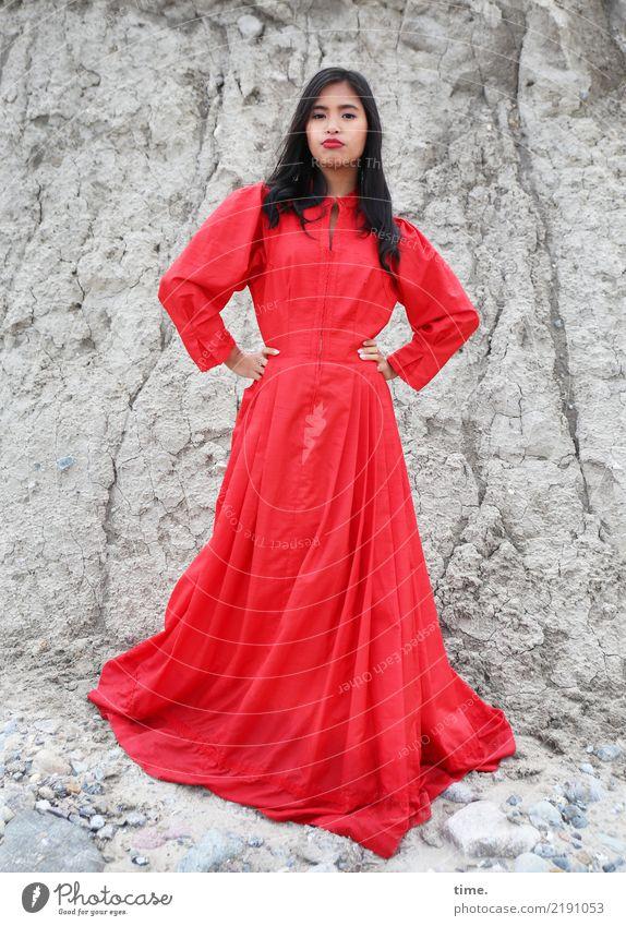Pinkaholickaye feminin Frau Erwachsene 1 Mensch Felsen Kleid schwarzhaarig langhaarig beobachten festhalten Blick stehen grau rot Willensstärke Mut Ausdauer