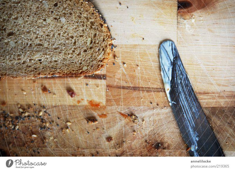 Moin - Frühstück! Lebensmittel Brot Krümel Brotkrümel Ernährung Abendessen Bioprodukte Vegetarische Ernährung Messer Schneidebrett Tisch braun Körnerbrot