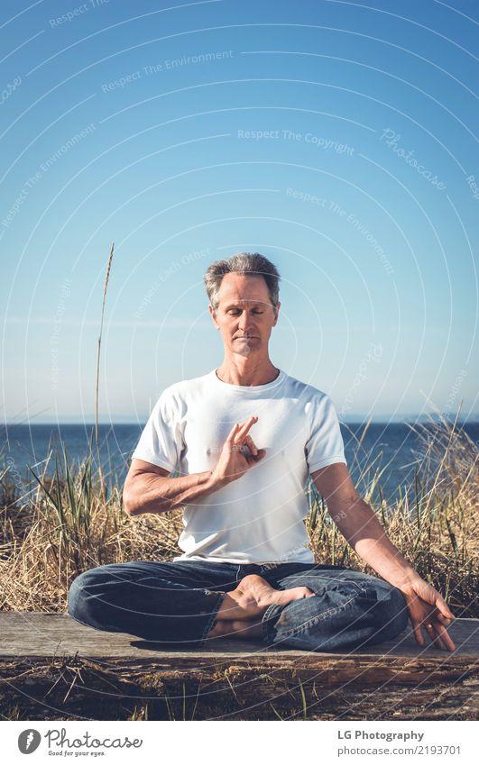 Mann, der in einer entspannten Yogahaltung am Strand sitzt. Sonne Erholung Erwachsene natürlich Kraft sitzen Aktion Gelassenheit Verstand Meditation üben