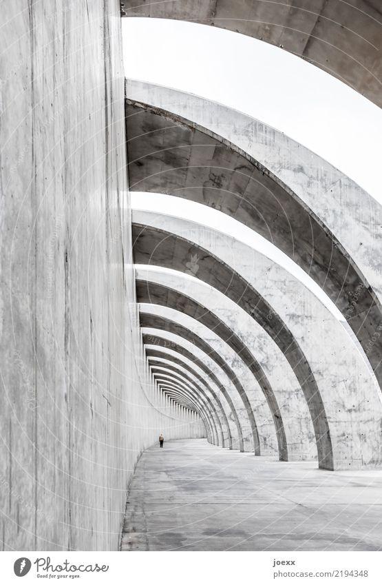 Modernes Sichtbeton Bauwerk, Mauer mit Bögen und Spaziergänger Hafenmauer Schutz Wellenbrecherdamm Architektur Breakwaters Beton Mann modern Bogen Schatten