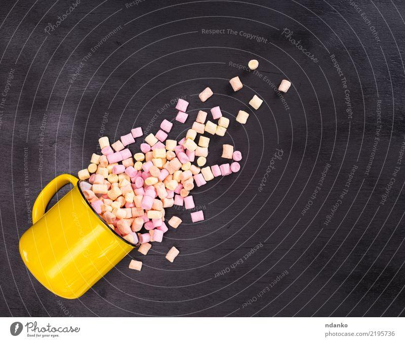 Stücke von farbigen Marshmallows Dessert Süßwaren Tasse Becher Tisch Holz Essen lecker weich gelb rosa schwarz weiß Hintergrund farbenfroh Bonbon Pastell