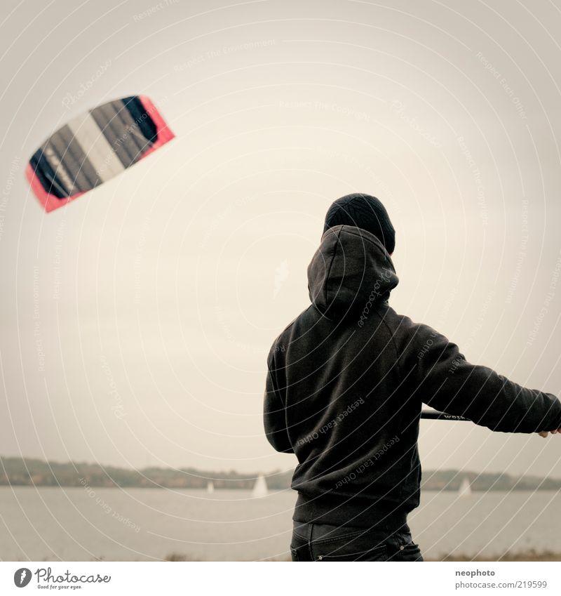 abheben Mensch Natur Herbst Sport See Wind fliegen Freizeit & Hobby Junger Mann Mütze Lenkdrachen Kiting gleiten Geschicklichkeit Spielzeug Rückansicht
