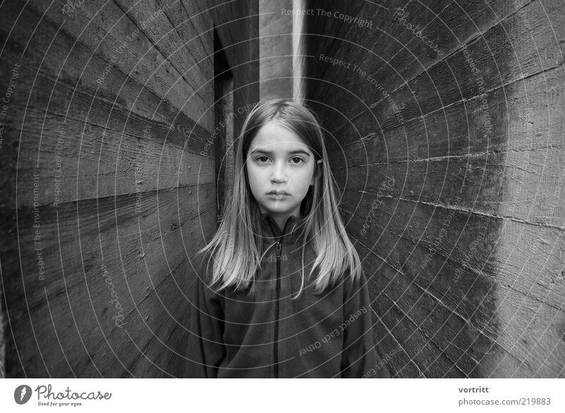 hypnotisierend Kind Mädchen 1 Mensch 8-13 Jahre Kindheit Bauwerk Gebäude Mauer Wand blond langhaarig Scheitel Stein Beton Blick stehen grau Gefühle Traurigkeit