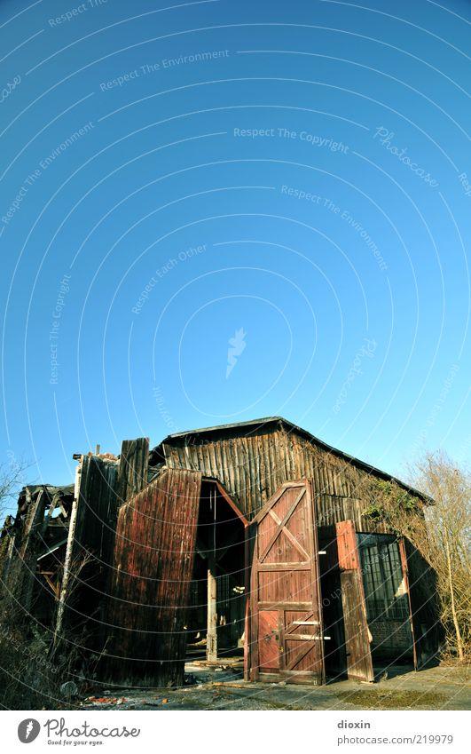 baufällig alt Himmel Baum Gebäude Sträucher kaputt Tor verfallen Verfall Bauwerk Lagerhalle Schönes Wetter Halle Wolkenloser Himmel Hallentor