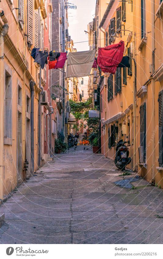 Blick in eine Gasse mit Wäsche auf einer Wäscheleine zwischen den Häusern Kérkira Korfu Hauptstadt Altstadt Haus Fassade Motorrad Kleinmotorrad Reinigen