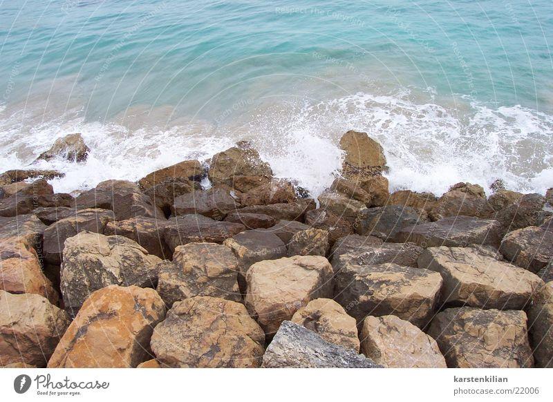 Steine als Wellenbrecher Wasser Meer blau Strand Küste Bucht Riff Buhne
