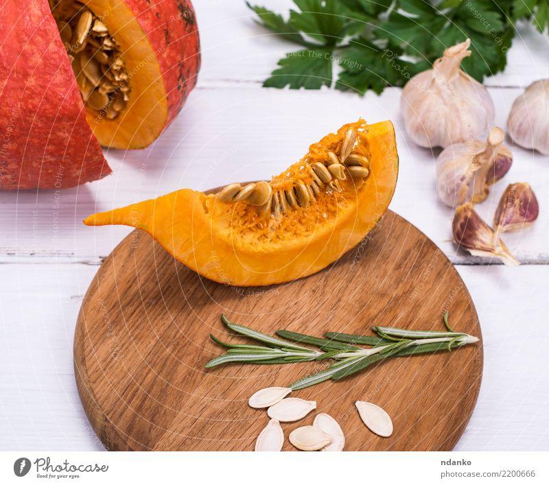 Stück frischer Kürbis mit Samen Gemüse Suppe Eintopf Essen Abendessen Vegetarische Ernährung Dekoration & Verzierung Tisch Halloween Natur Herbst Holz gelb