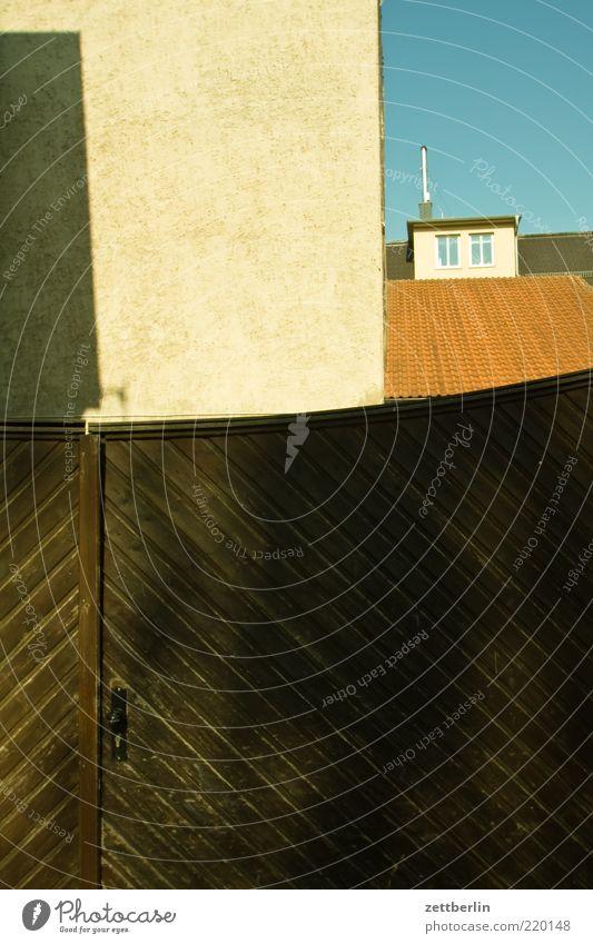 Hoftor Tür Tor Eingangstor Ausgang Haus geschlossen Exil Holztor Fassade Ecke Dach Dachfenster Textfreiraum unten Schatten Putz Blauer Himmel Menschenleer