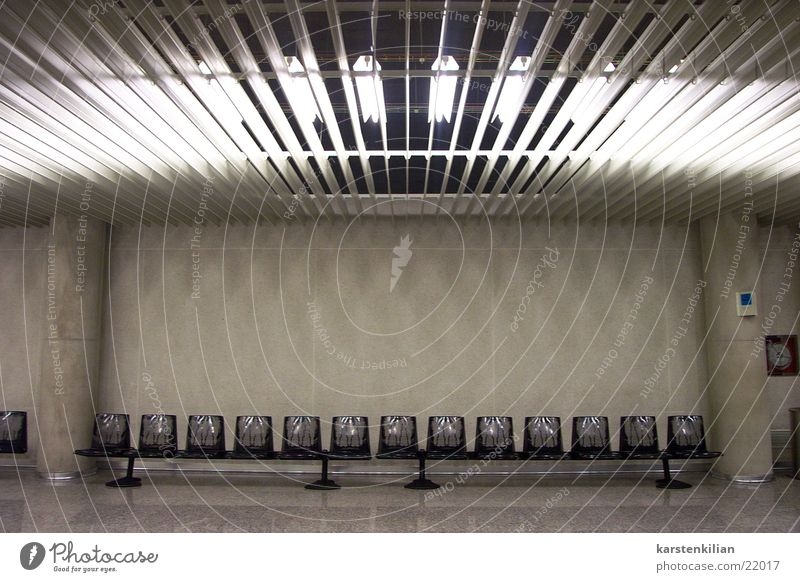 Unscheinbarer Wartesaal Licht Neonlicht grau Beton Stuhl Sitzreihe Warteraum Architektur Lagerhalle Säule Bank künstliches Licht leer