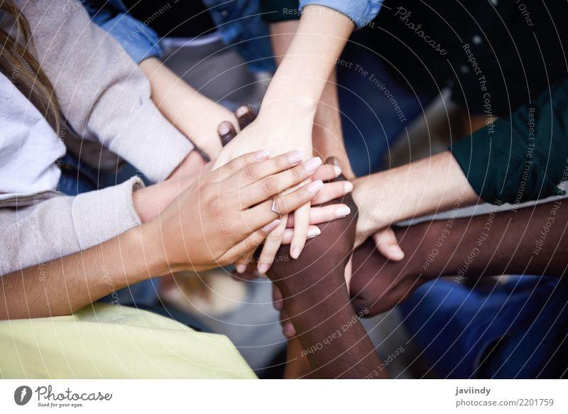 Mehrrassige junge Menschen, die ihre Hände zusammenstecken. Lifestyle Frau Erwachsene Mann Freundschaft Hand 5 Menschengruppe 18-30 Jahre Jugendliche