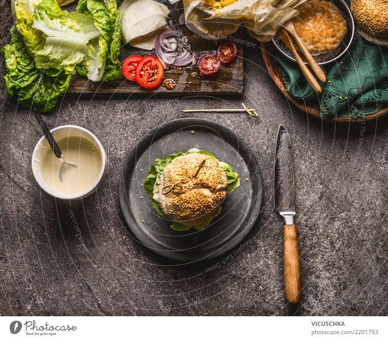 Hausgemachter Burger auf dem Teller mit Messer und Zutaten Lebensmittel Fleisch Käse Gemüse Salat Salatbeilage Brötchen Ernährung Mittagessen Fastfood Geschirr