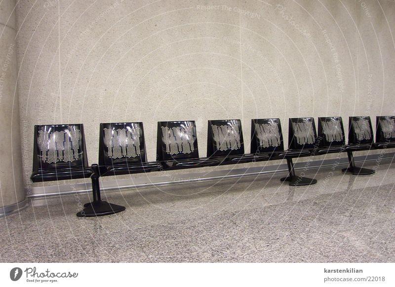 Reihenweise schwarz kalt grau Raum warten Bank Sitzreihe steril Abflughalle Saal unpersönlich Betonwand Wartesaal