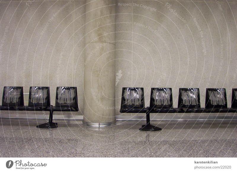 Sitzreihe unterbrochen Wartesaal Beton schwarz grau Betonwand steril unpersönlich kalt Architektur Abflughalle Bank Säule Raum warten