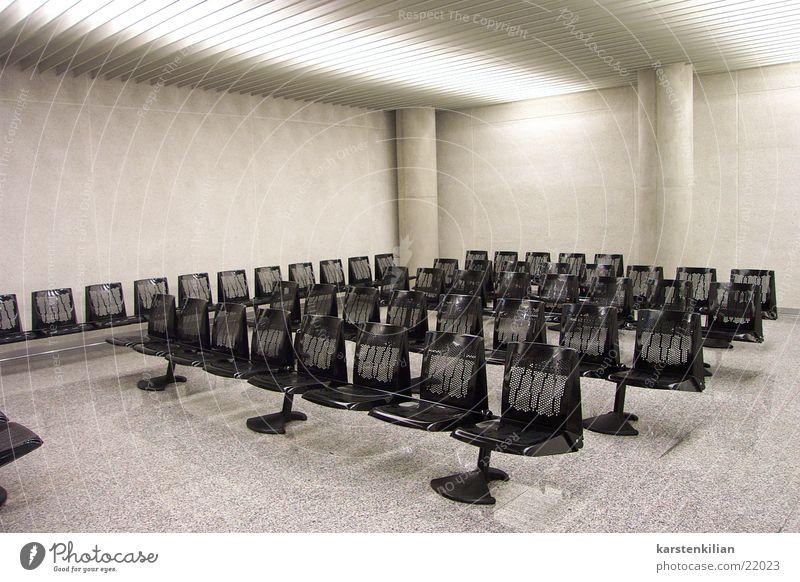 Wartesaal in grau Bank Sitzreihe Saal Beton schwarz unpersönlich Architektur Sitzgruppe Lagerhalle künstliches Licht