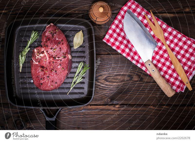 rohes Rindersteak mit Gewürzen Lebensmittel Fleisch Kräuter & Gewürze Abendessen Messer Gabel Tisch Küche Holz Essen frisch grün rot Bratpfanne Serviette