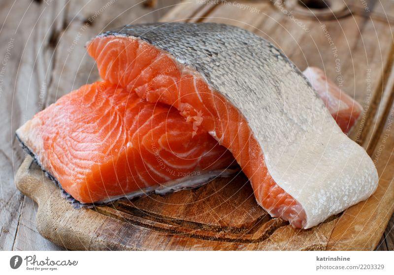 Frische rohe Lachse auf einem hölzernen Schneidebrett Fisch Meeresfrüchte Ernährung Essen Abendessen Diät Tisch frisch rot Hintergrund Holzplatte