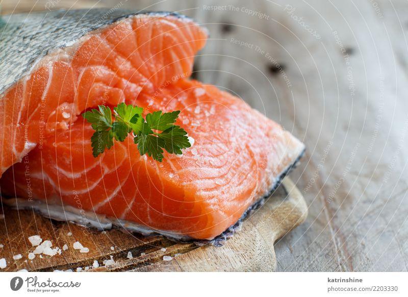 Frische rohe Lachse auf einem hölzernen Schneidebrett Fisch Meeresfrüchte Ernährung Essen Abendessen Diät Tisch frisch grün rot Hintergrund Holzplatte