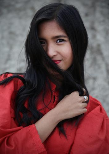 Pinkaholickaye feminin Frau Erwachsene 1 Mensch Felsen Kleid Ring schwarzhaarig langhaarig beobachten festhalten Lächeln Blick schön grau rot Freude