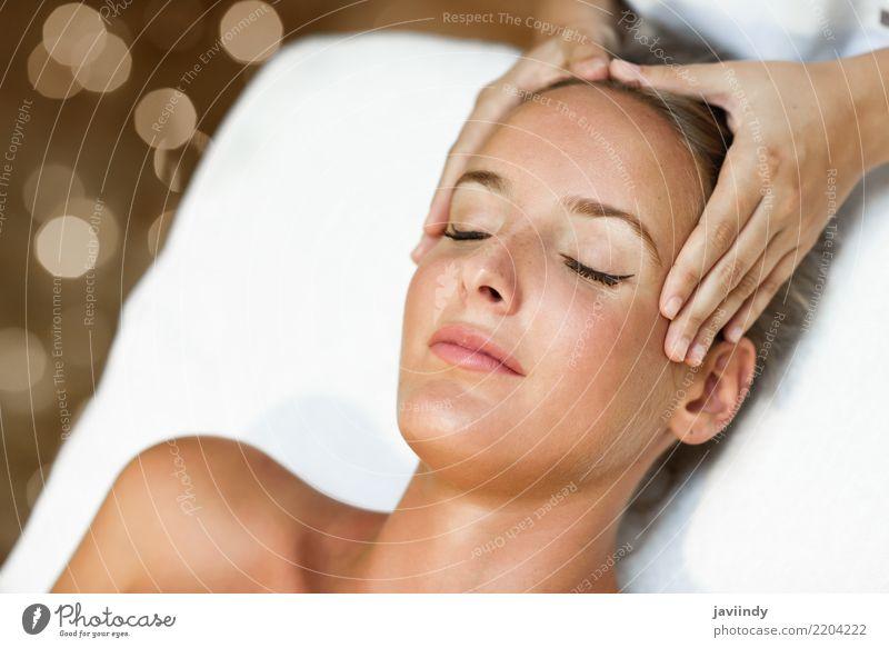 Junge blonde Frau, die eine Kopfmassage in einer Badekurortmitte empfängt Mensch schön Hand Erholung Gesicht Erwachsene Lifestyle Gesundheitswesen Haut