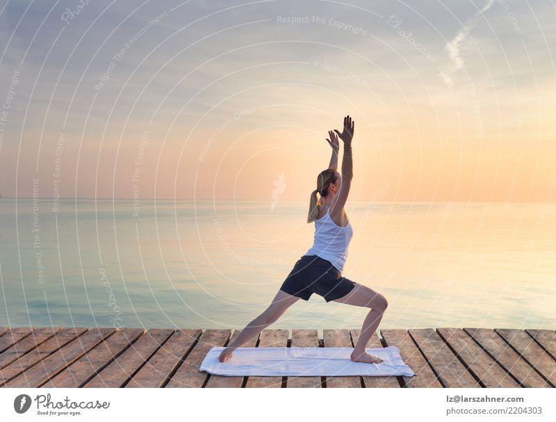 Übendes Yoga der jungen Frau durch Meer Mensch Ferien & Urlaub & Reisen Sommer Erholung Erwachsene Textfreiraum blond Kraft stehen Energie Wellness Gelassenheit