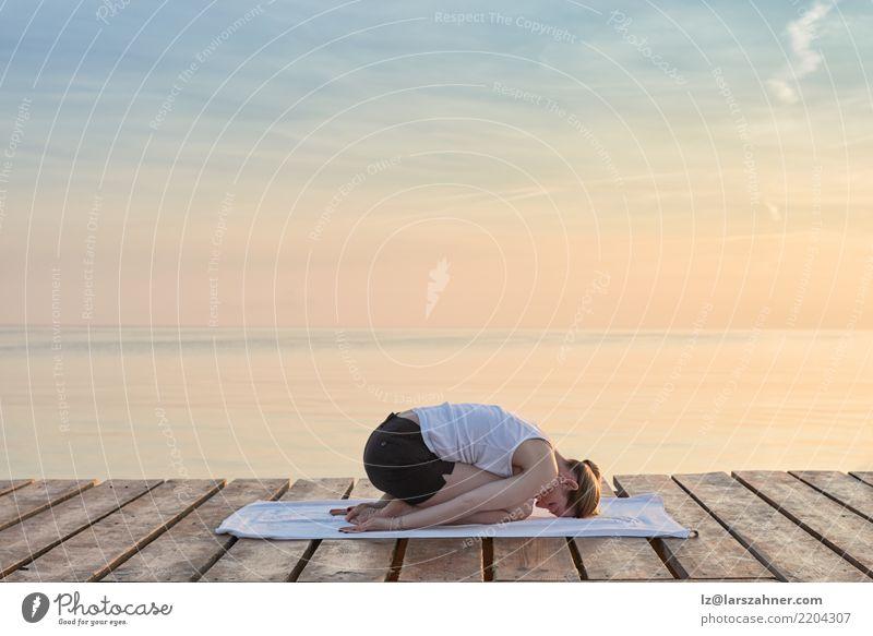 Übendes Yoga der jungen Frau durch Meer Ferien & Urlaub & Reisen Sommer Erholung Erwachsene Textfreiraum blond Kraft Energie Wellness Gelassenheit Meditation