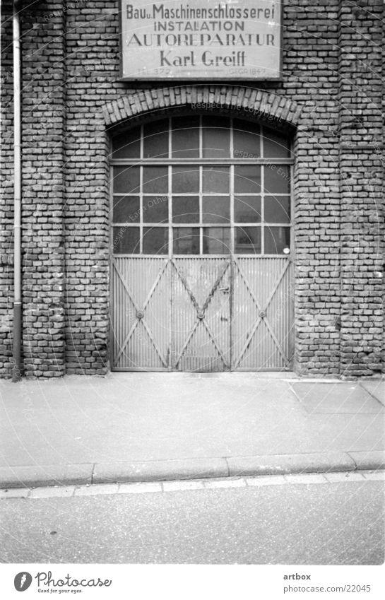 Karl Greifs Werkstatt retro Vergangenheit Autowerkstatt Handwerk Quadrat Backstein historisch Tor garu Schwarzweißfoto alt Metall Einsamkeit früher