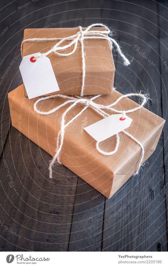 Zwei überlagerte Geschenke mit Etiketten Handarbeit Feste & Feiern Silvester u. Neujahr Geburtstag Paket Schnur Überraschung schwarzer Hintergrund Braunwickel