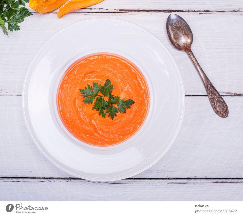 Teller mit Kürbiscremesuppe Gemüse Suppe Eintopf Essen Mittagessen Abendessen Vegetarische Ernährung Diät Löffel Tisch Herbst Holz frisch heiß oben gelb weiß