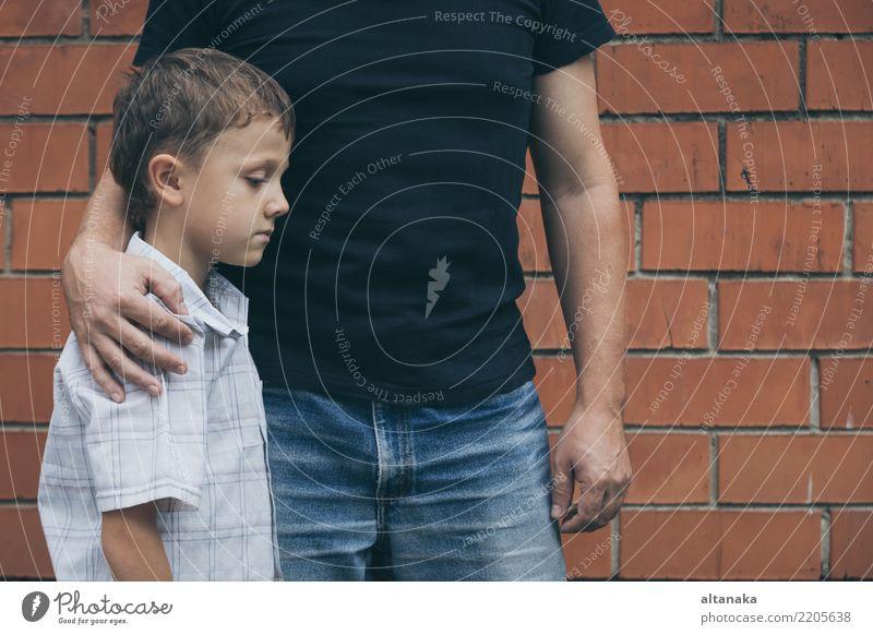 Porträt von jungen traurigen kleinen Jungen und Vater sitzen im Freien an der Tageszeit. Konzept der Traurigkeit. Gesicht Kind Mann Erwachsene Eltern