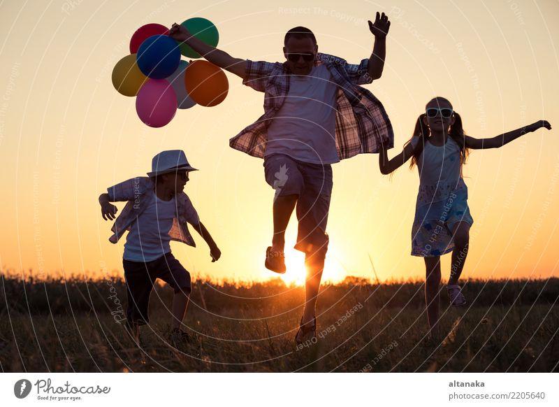 Vater und Kinder rennen zur Zeit des Sonnenuntergangs auf der Straße. Konzept der glücklichen Familie. Lifestyle Freude Glück Freizeit & Hobby