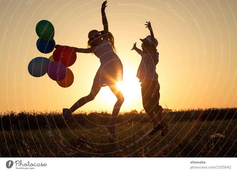 Schattenbild von zwei glücklichen Kindern, die auf dem Feld spielen Lifestyle Freude Glück Freizeit & Hobby Spielen Ferien & Urlaub & Reisen Freiheit Camping