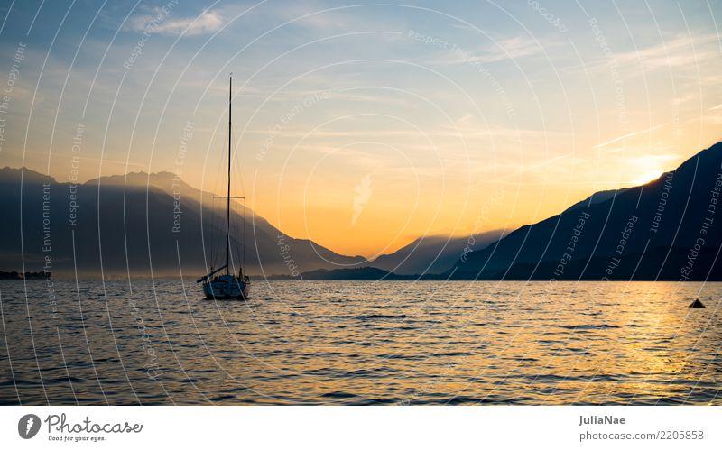 Sonnenaufgang am Comer See mit einem Boot auf dem Wasser lago die como Italien Berge u. Gebirge Alpen Morgen Sonnenstrahlen Morgendämmerung Nebel