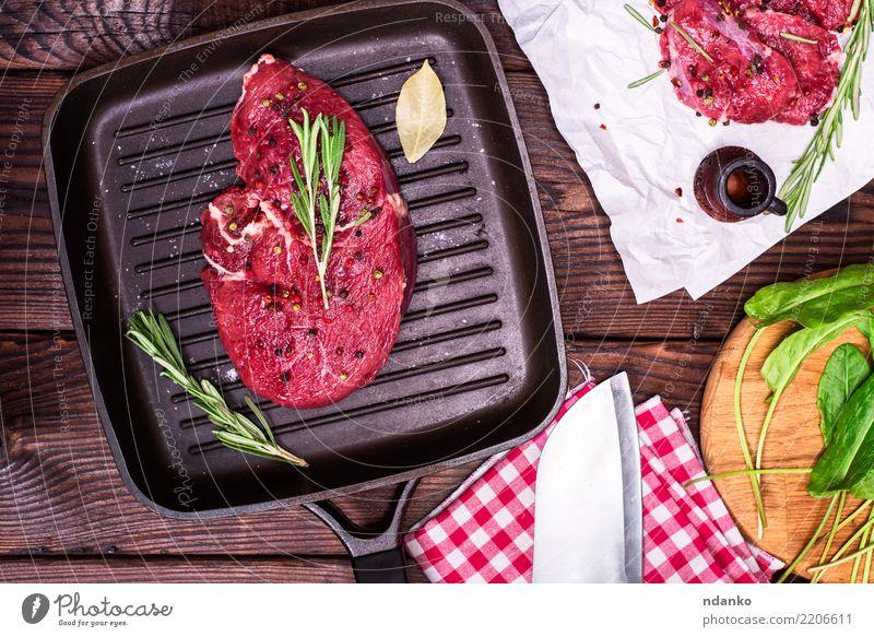 rohes Rindersteak in Gewürzen grün rot Holz frisch Aussicht Tisch Papier Kräuter & Gewürze Küche Abendessen Fleisch Mahlzeit Scheibe Top Blut geschnitten