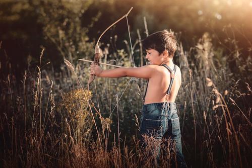 Bogenschütze Junge Kind Mensch Ferien & Urlaub & Reisen Wald Lifestyle Gefühle Bewegung Spielen Freiheit Freizeit & Hobby maskulin Feld Kindheit Abenteuer