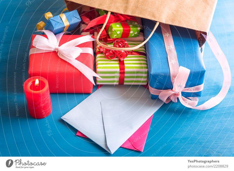 Bündel Geschenke, die aus eine Tasche herauskommen Glück Feste & Feiern Freundschaft Schnur Kerze Überraschung Silvester u. Neujahr Tüte Holztisch Handarbeit