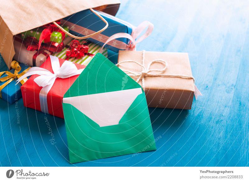 Geöffneter Umschlag und Tasche voller Geschenke Glück Feste & Feiern Freundschaft Schnur Kerze Überraschung Silvester u. Neujahr Tüte Holztisch Handarbeit