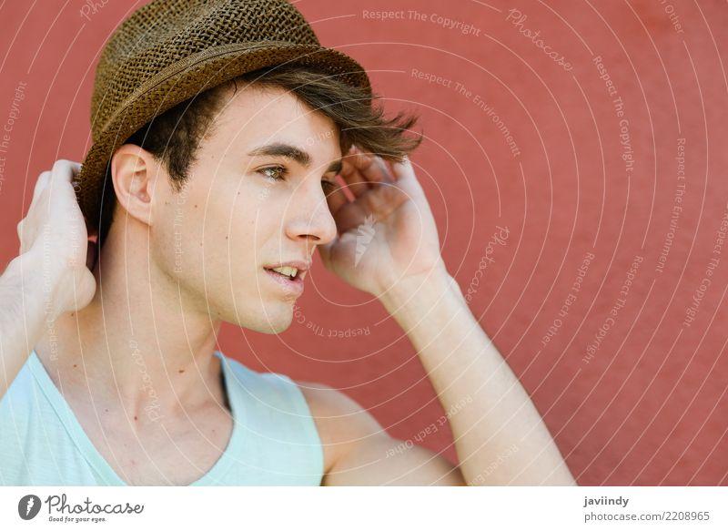Junger Mann im städtischen Hintergrund, der einen Sonnenhut trägt Lifestyle Stil Glück schön Mensch Erwachsene Straße Mode T-Shirt Hut Coolness frisch trendy