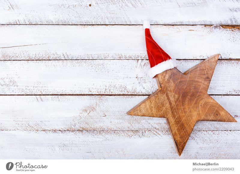 Stern mit Weihnachtsmütze auf weißem Holztisch Weihnachten & Advent rot Winter Symbole & Metaphern Mütze Vorfreude Weihnachtsmann Feiertag minimalistisch