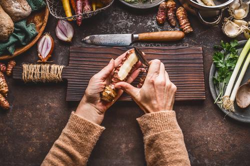 Weibliche Hände schälen Topinambur auf Küchentisch Lebensmittel Gemüse Suppe Eintopf Kräuter & Gewürze Öl Ernährung Mittagessen Abendessen Bioprodukte