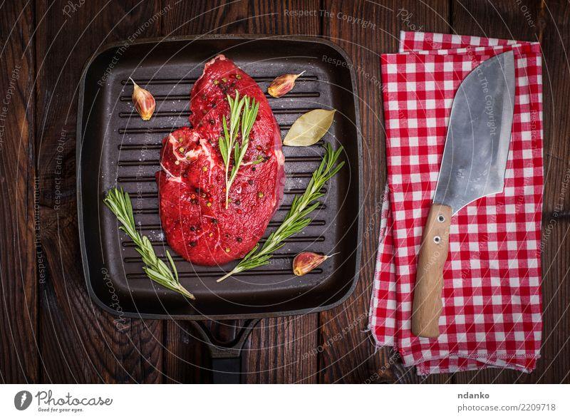 rohes Rindersteak in Gewürzen Lebensmittel Fleisch Kräuter & Gewürze Abendessen Pfanne Messer Tisch Holz Essen frisch braun grün rot Mahlzeit Rindfleisch
