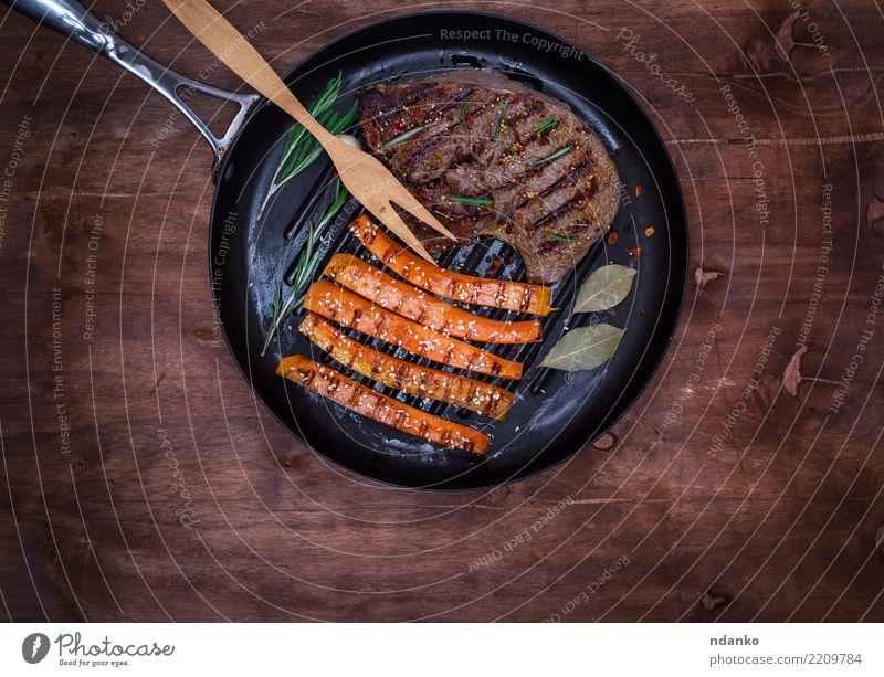 Bratpfanne mit einem Stück gebratenem Rindfleisch Fleisch Gemüse Kräuter & Gewürze Ernährung Mittagessen Pfanne Gabel Tisch Restaurant Holz heiß lecker oben