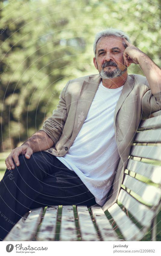 Nachdenklicher reifer Mann, der auf einer Bank in einem städtischen Park sitzt Mensch alt weiß Freude Erwachsene Straße Lifestyle Senior Glück maskulin