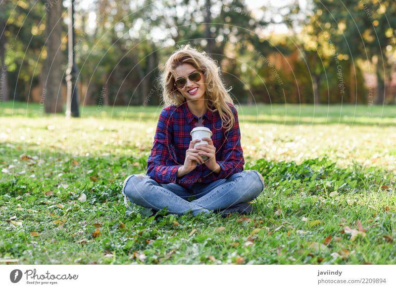 Trinkender Kaffee des blonden Mädchens im Park, der auf Gras sitzt Tee Lifestyle Freude Glück schön Haare & Frisuren Erholung Mensch Frau Erwachsene Natur