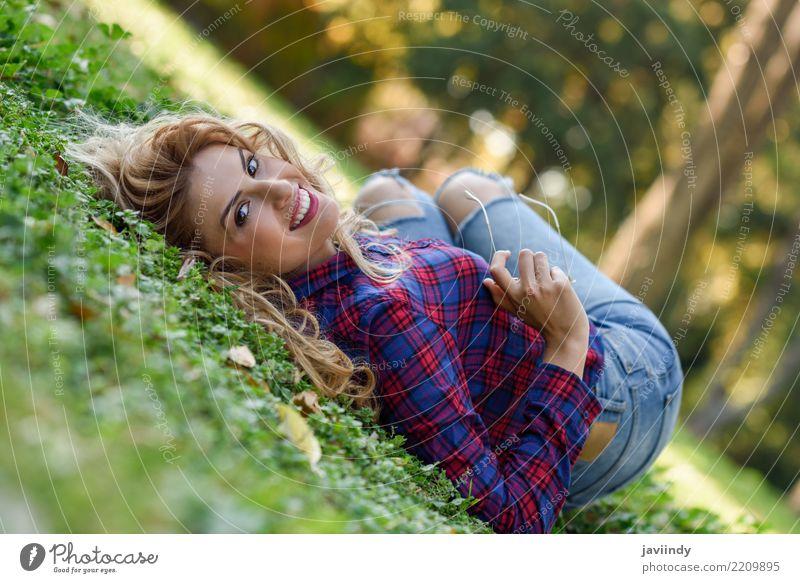 Junge Frau mit dem langen blonden gelockten Haar, das auf Gras legt Lifestyle Freude Glück schön Haare & Frisuren Erholung Mensch feminin Jugendliche Erwachsene